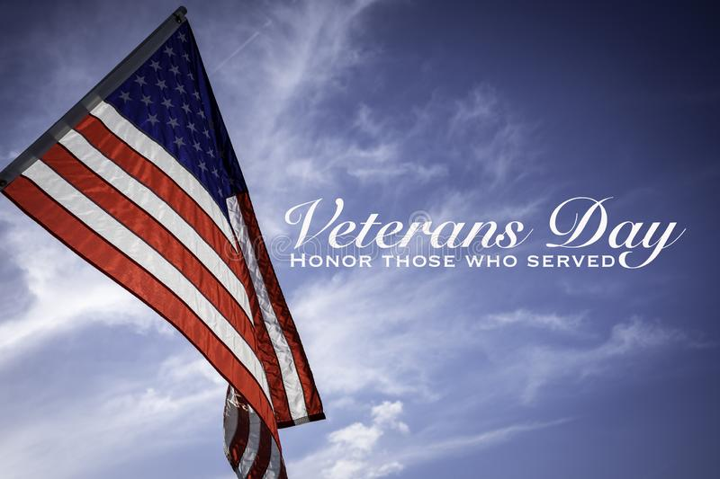 American flags with a Veterans Day greeting. With blue sky baacakground royalty free stock photo