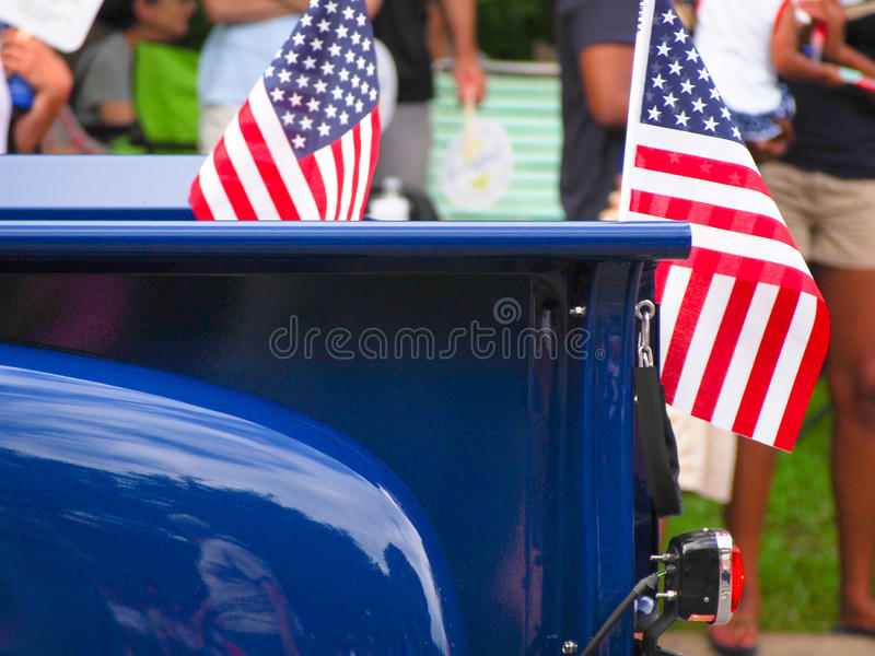 American Flags on Vintage Truck for Independence Day Parade. American flags attached to a bright blue classic truck driving in a Fourth of July parade royalty free stock photography