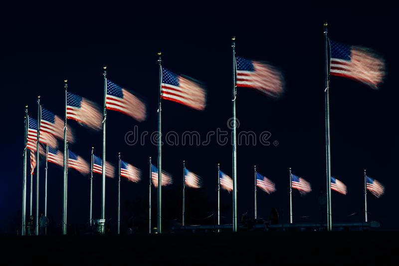 American flags at the Washington Monument at night, in Washington, DC.  stock photography