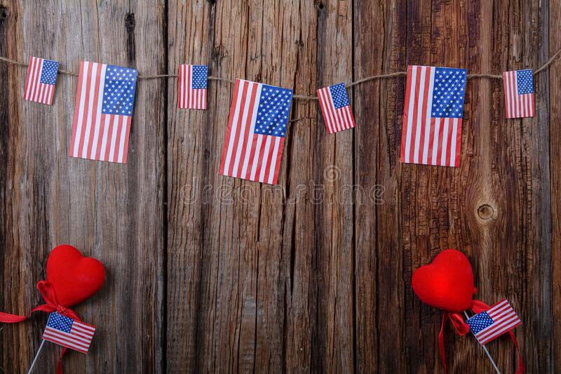American flags on a wooden background with a heart and roses stock photos