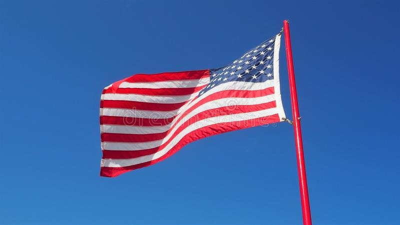 American flying flag. Flying American flag in the blue sky royalty free stock photography