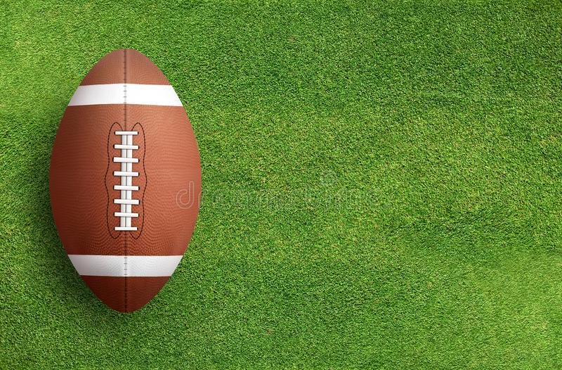 American football ball on grass field background. stock photography