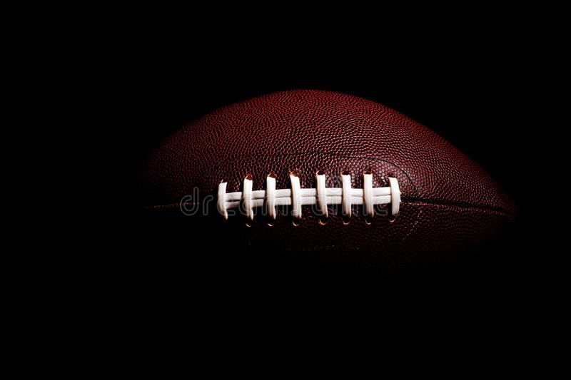 American football ball isolated on black background. Activity brown closeup college competition energy equipment game lace leather nfl object oval pigskin play royalty free stock photography