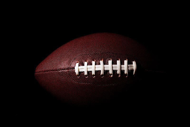 American football ball isolated on black background. Activity brown closeup college competition energy equipment game lace leather nfl object oval pigskin play stock images