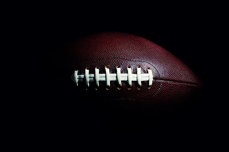 American football ball isolated on black background. Activity, brown, closeup, college, competition, energy, equipment, game, lace, leather, nfl, object, oval royalty free stock photo