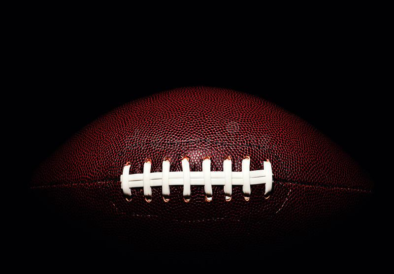 American football ball isolated on black background. Activity, brown, closeup, college, competition, energy, equipment, game, lace, leather, nfl, object, oval royalty free stock images