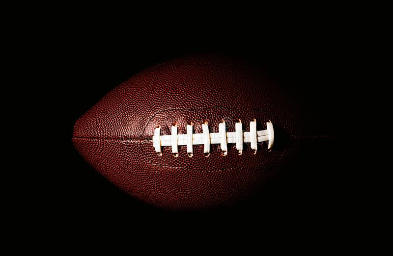 American football ball isolated on black background. Activity, brown, closeup, college, competition, energy, equipment, game, lace, leather, nfl, object, oval stock photography