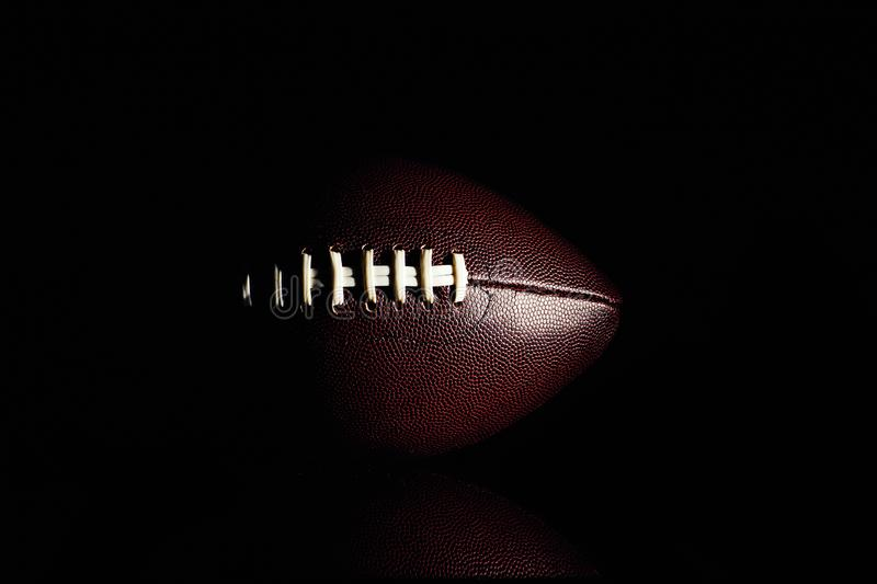 American football ball isolated on black background. Activity, brown, closeup, college, competition, energy, equipment, game, lace, leather, nfl, object, oval stock images