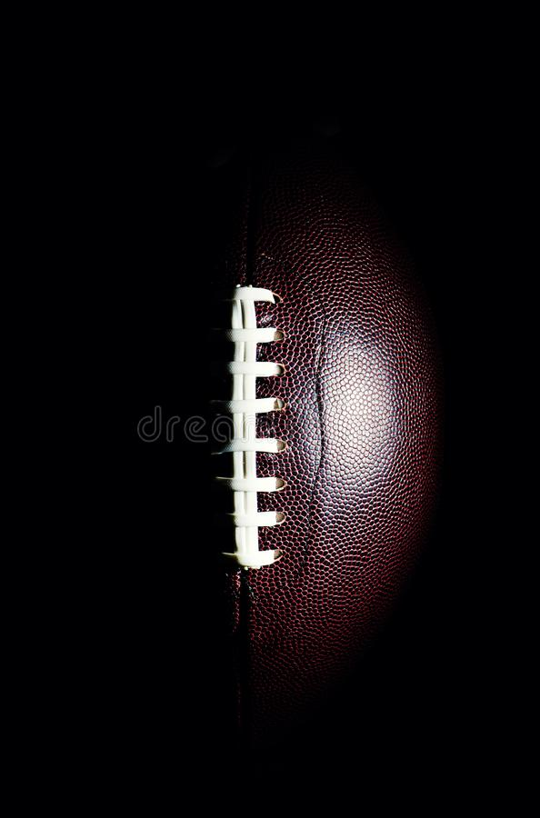 American football ball isolated on black background. Activity, brown, closeup, college, competition, energy, equipment, game, lace, leather, nfl, object, oval stock image