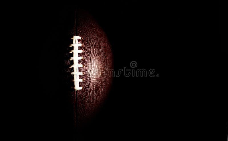 American football ball isolated on black background. Activity, brown, closeup, college, competition, energy, equipment, game, lace, leather, nfl, object, oval royalty free stock image