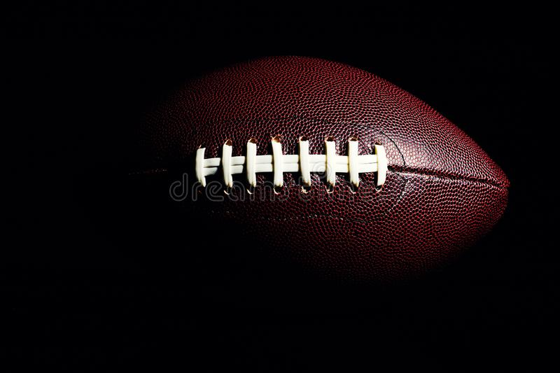 American football ball isolated on black background. Activity, brown, closeup, college, competition, energy, equipment, game, lace, leather, nfl, object, oval royalty free stock photos