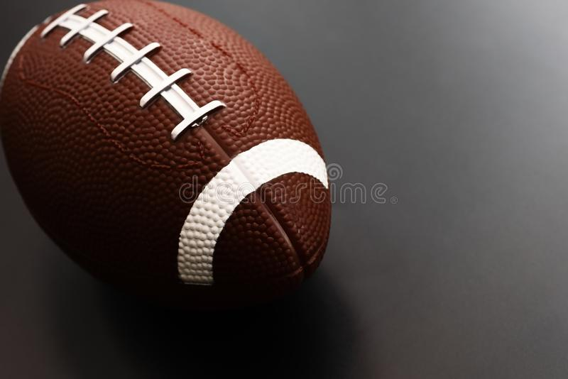 American football on black background. Sport object concept stock photo
