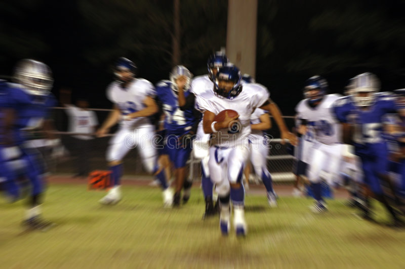 American football blur. American football action with a player running with ball (zoom motion blur) during a night game stock images