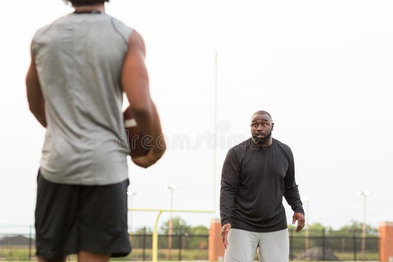 American Football coach training a young athlete. royalty free stock photos