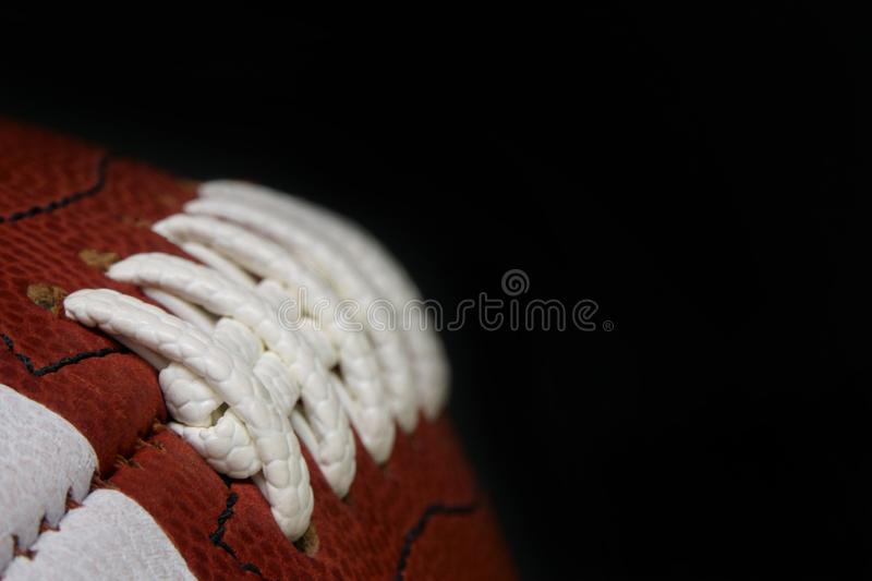 American Football Game Ball Laces and Texture Detail Against a Black Background royalty free stock images