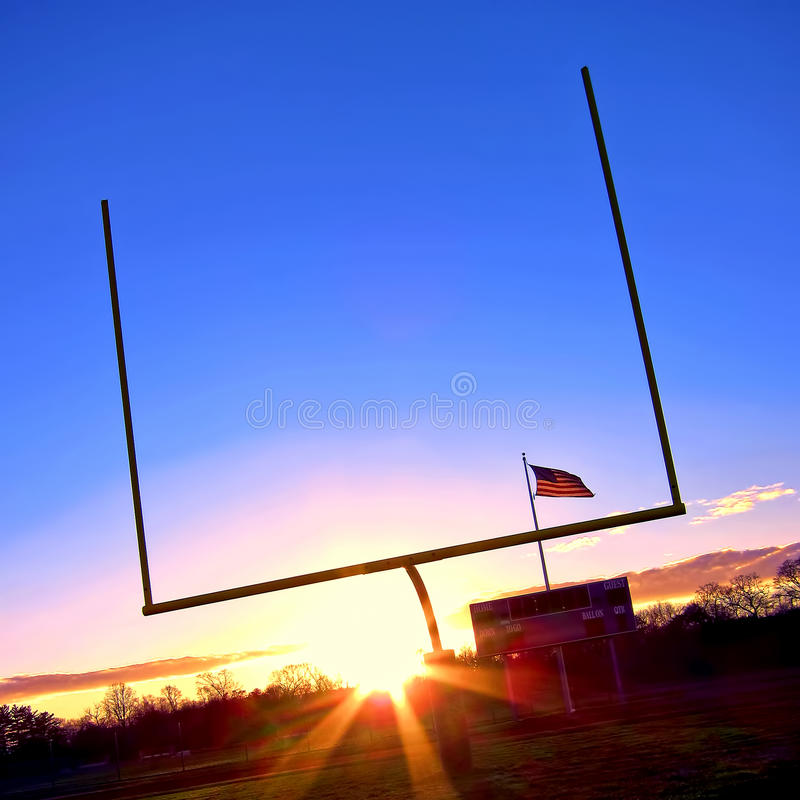 American Football Goal Posts and US Flag at Sunset. American football goal posts at end zone with stadium score board and US flag post at sunset over blue sky stock images