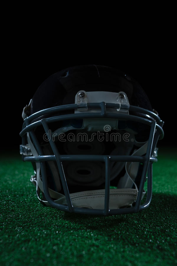 American football head gear on artificial turf. Against a black background stock photography