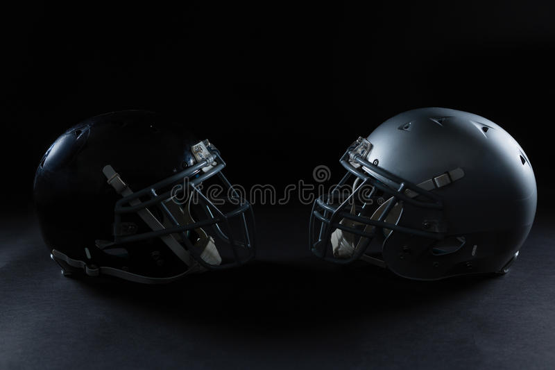 American football head gear facing each other. Against a black background royalty free stock photography