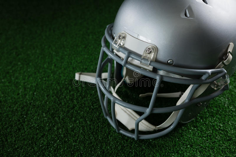 American football head gear over artificial turf. Close-up of American football head gear over artificial turf royalty free stock photography