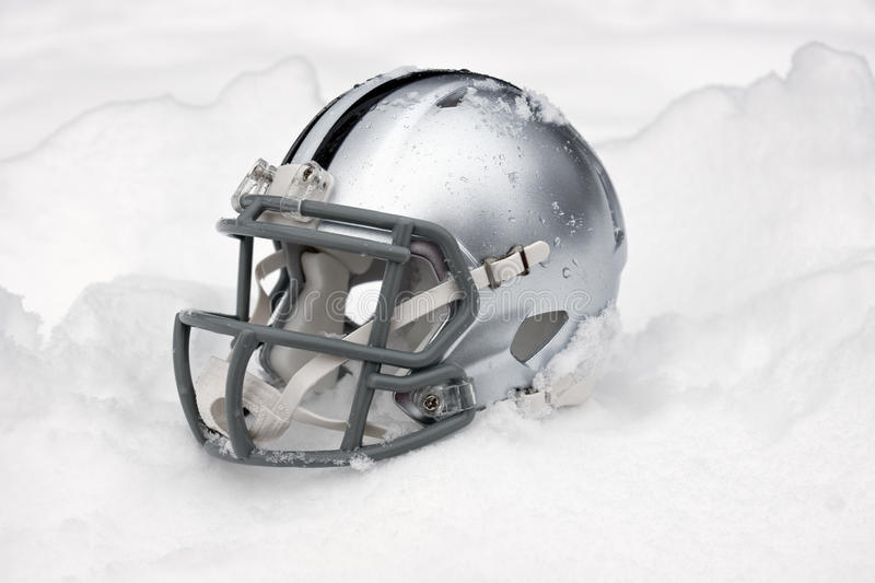 American football helmet in snow. American football helmet covered in the snow and ice stock images