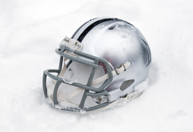American football helmet in snow. American football helmet covered in the snow and ice royalty free stock photography