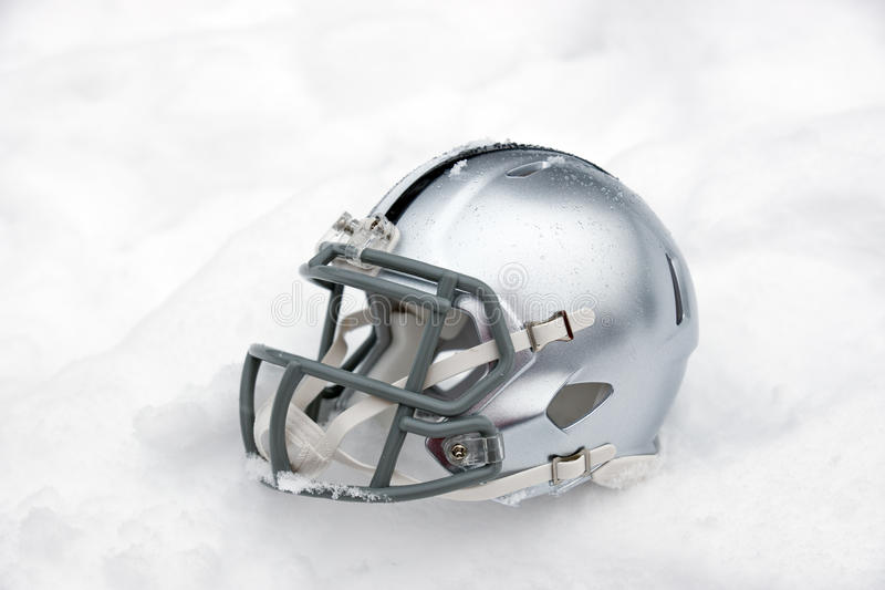 American football helmet in snow. American football helmet covered in the snow and ice royalty free stock image