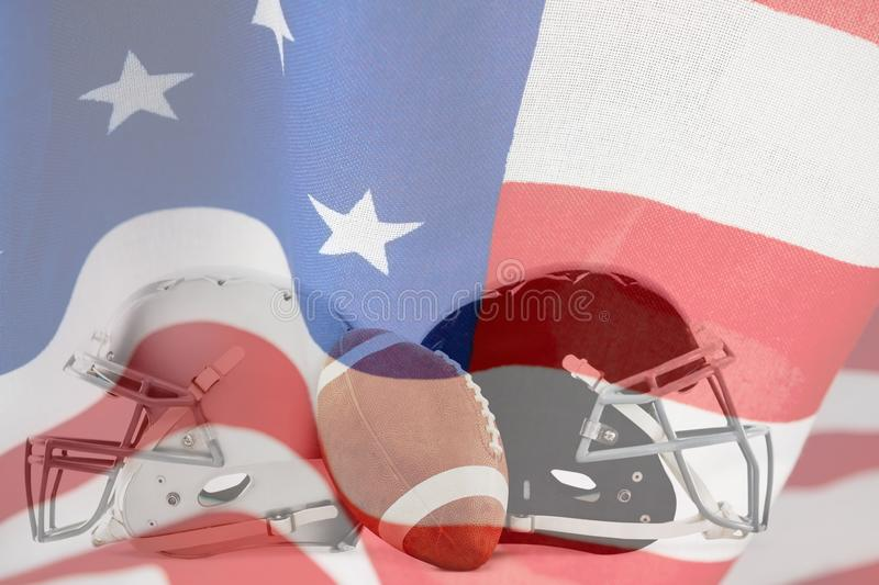 Composite image of american football with helmets. American football with helmets against close-up of an american flag stock image