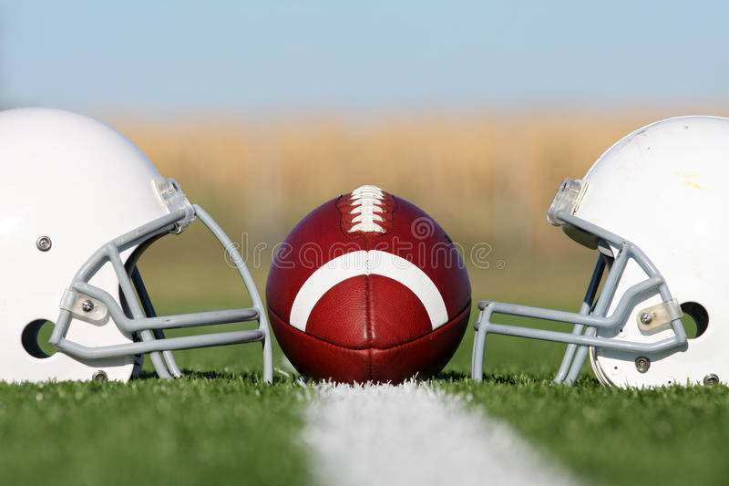 American Football with Helmets on the Field royalty free stock image