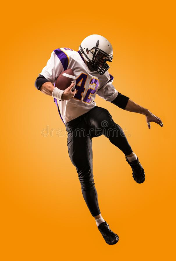 American football player in action. High jump of American football player royalty free stock photography