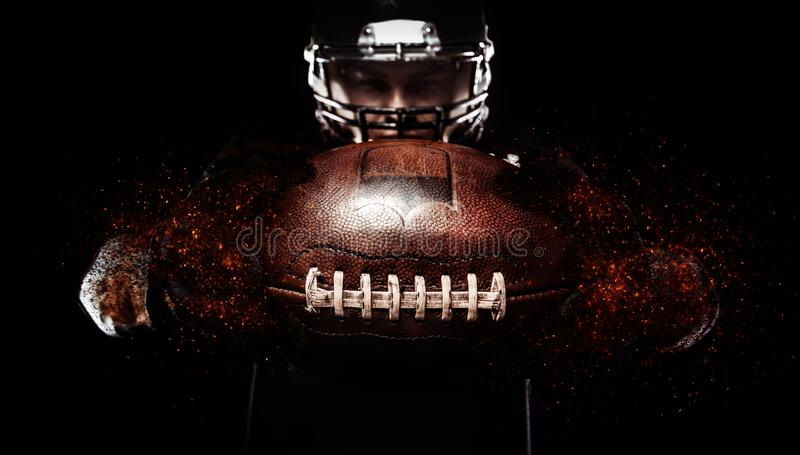 American football player, athlete in helmet with ball on black background. Sport wallpaper with copyspace. stock photo