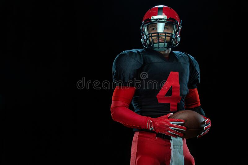 American football player, athlete sportsman in red helmet on black background. Sport and motivation wallpaper. royalty free stock photos