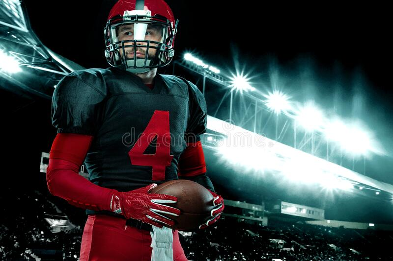 American football player, athlete sportsman in red helmet on stadium background. Sport and motivation wallpaper. royalty free stock photography