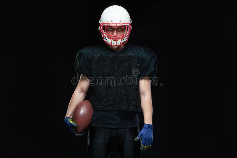 American football player in a black uniform, wearing helmet and holding ball against black background royalty free stock photos