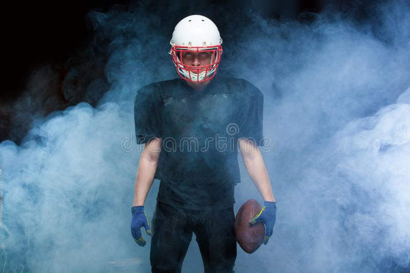 American football player in a black uniform, wearing helmet and holding ball against white smoke royalty free stock photo