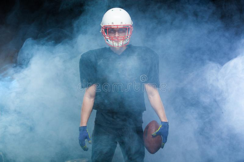 American football player in a black uniform, wearing helmet and holding ball against white smoke stock photo