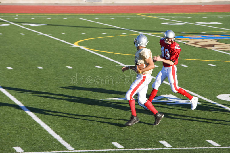 American football player chasing opposing receiver with ball during competitive game, side view royalty free stock images