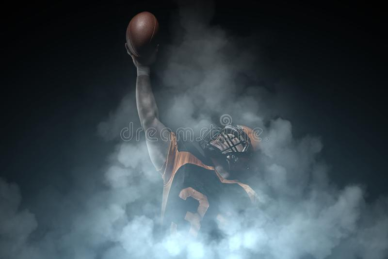 American football player on a dark background in smoke in black and orange equipment royalty free stock photo