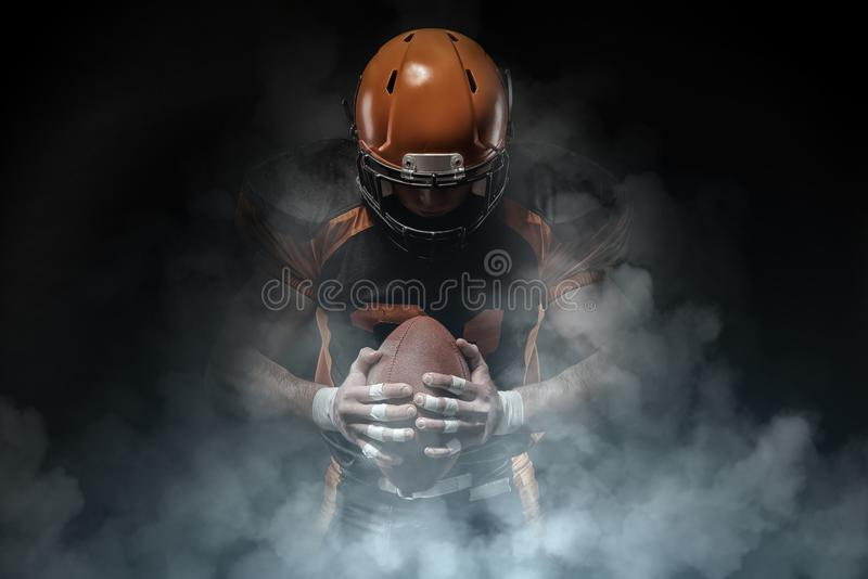 American football player on a dark background in smoke in black and orange equipment royalty free stock image