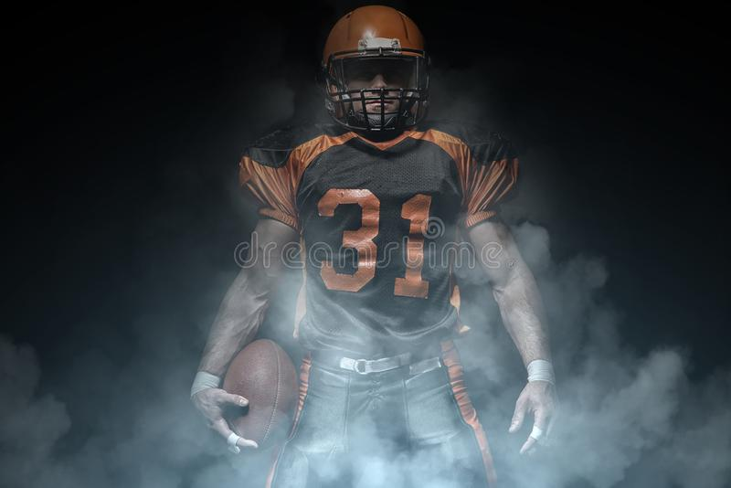 American football player on a dark background in smoke in black and orange equipment royalty free stock photography