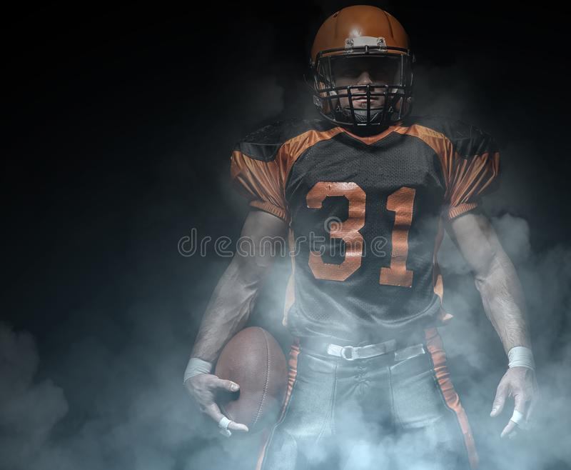 American football player on a dark background in smoke in black and orange equipment royalty free stock photos
