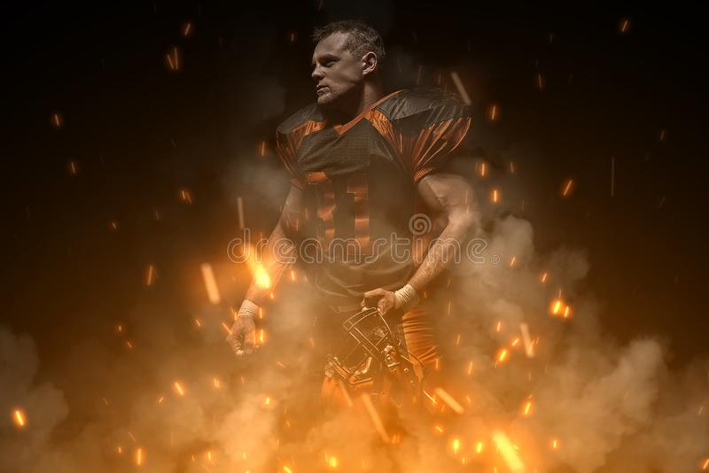 American football player on dark background in smoke and sparks in black and orange outfit stock photography