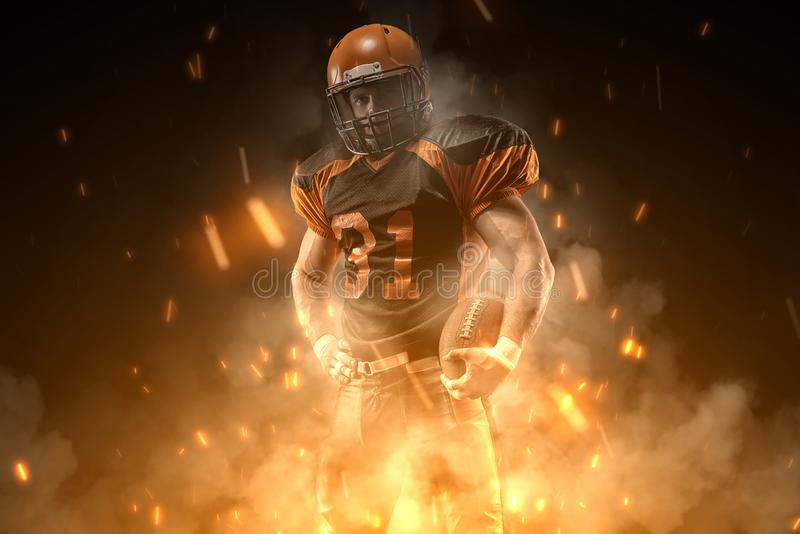 American football player on dark background in smoke and sparks in black and orange outfit stock photos