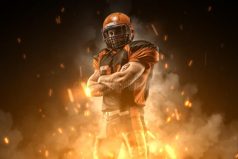 American football player on dark background in smoke and sparks in black and orange outfit royalty free stock photo