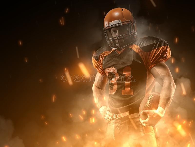 American football player on dark background in smoke and sparks in black and orange outfit royalty free stock photography