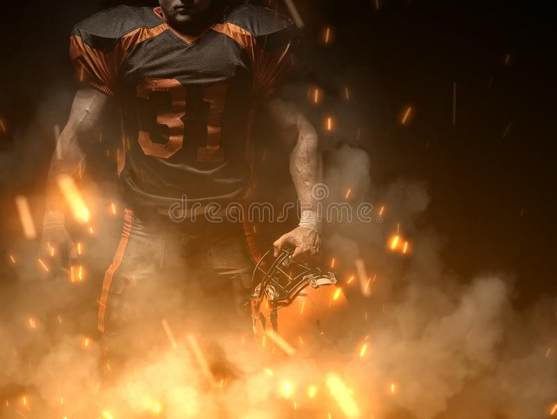 American football player on dark background in smoke and sparks in black and orange outfit royalty free stock photos