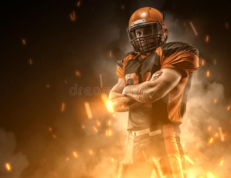 American football player on dark background in smoke and sparks in black and orange outfit stock photo