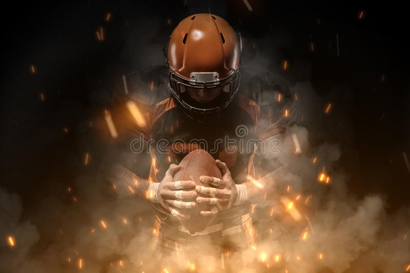 American football player on dark background in smoke and sparks in black and orange outfit stock image