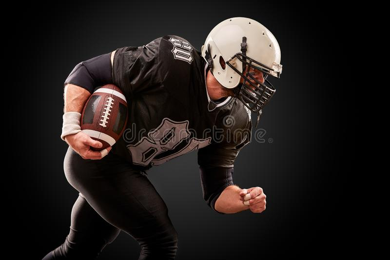 American football player in dark uniform with the ball is preparing to attack on a black background. stock photo