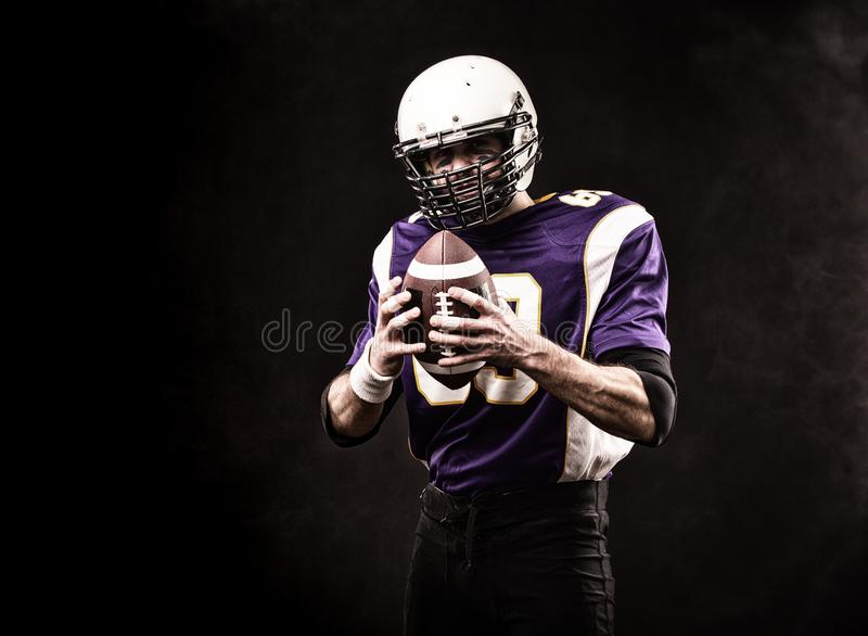 American football player holding the ball in his hands. Black background, copy space. The concept of American football royalty free stock image