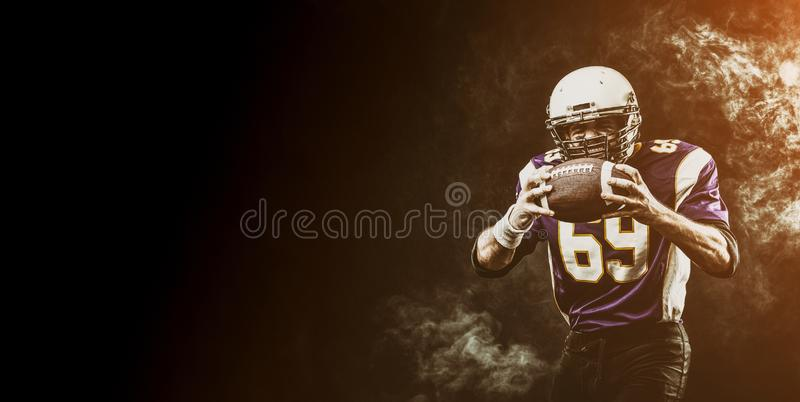 American football player holding ball in his hands in smoke. Black background, copy space. The concept of American stock image